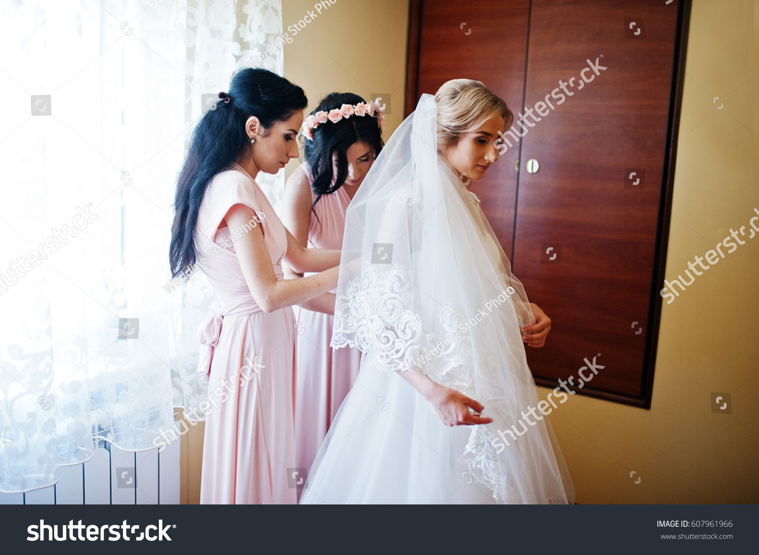10c573d4d373 Fashionable bridesmaids on pink dresses helped wear bow on back of wedding  dress bride. Morning