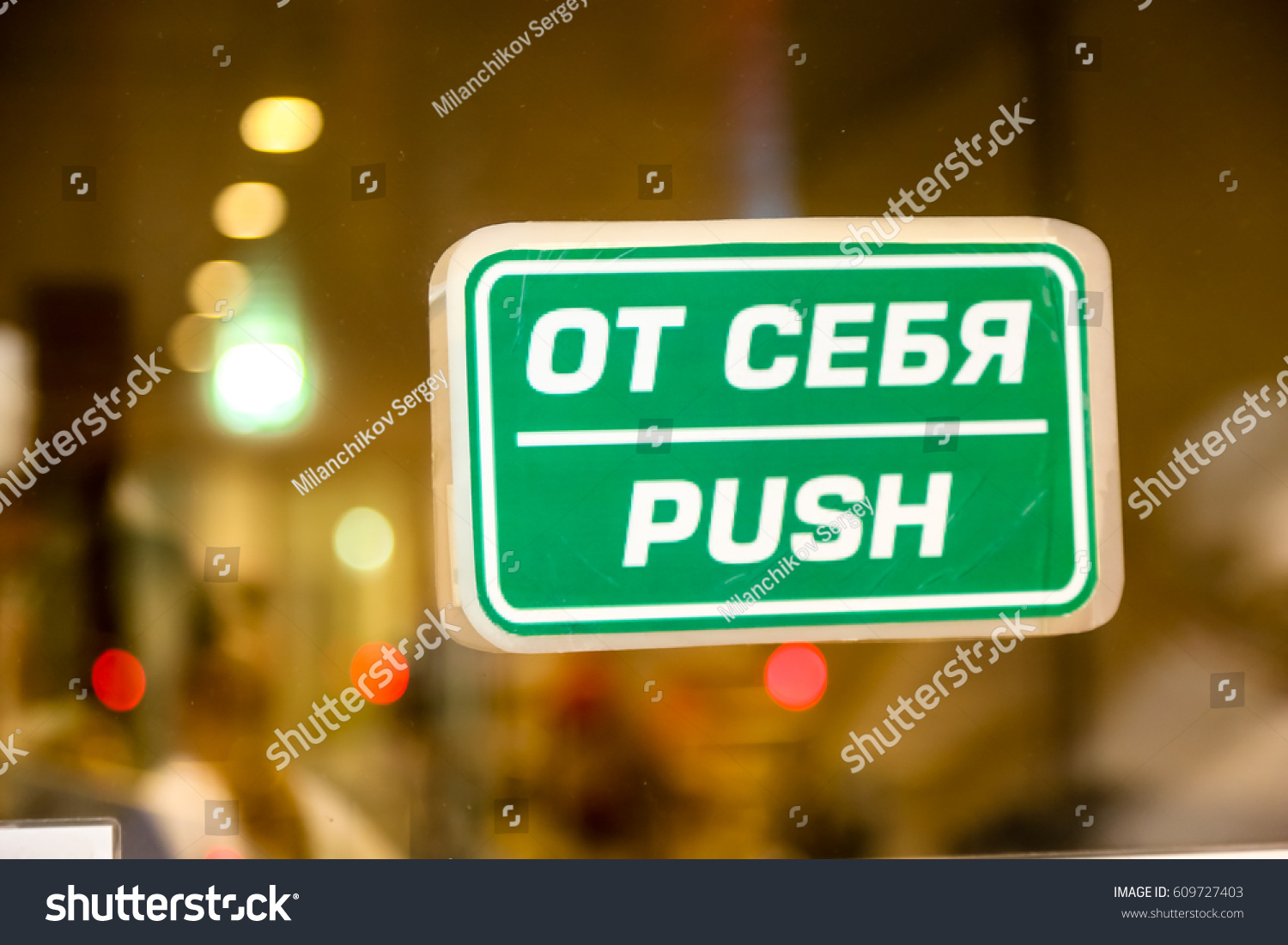 Sign Push In Russian And English On The Glass Door Behind Which Some