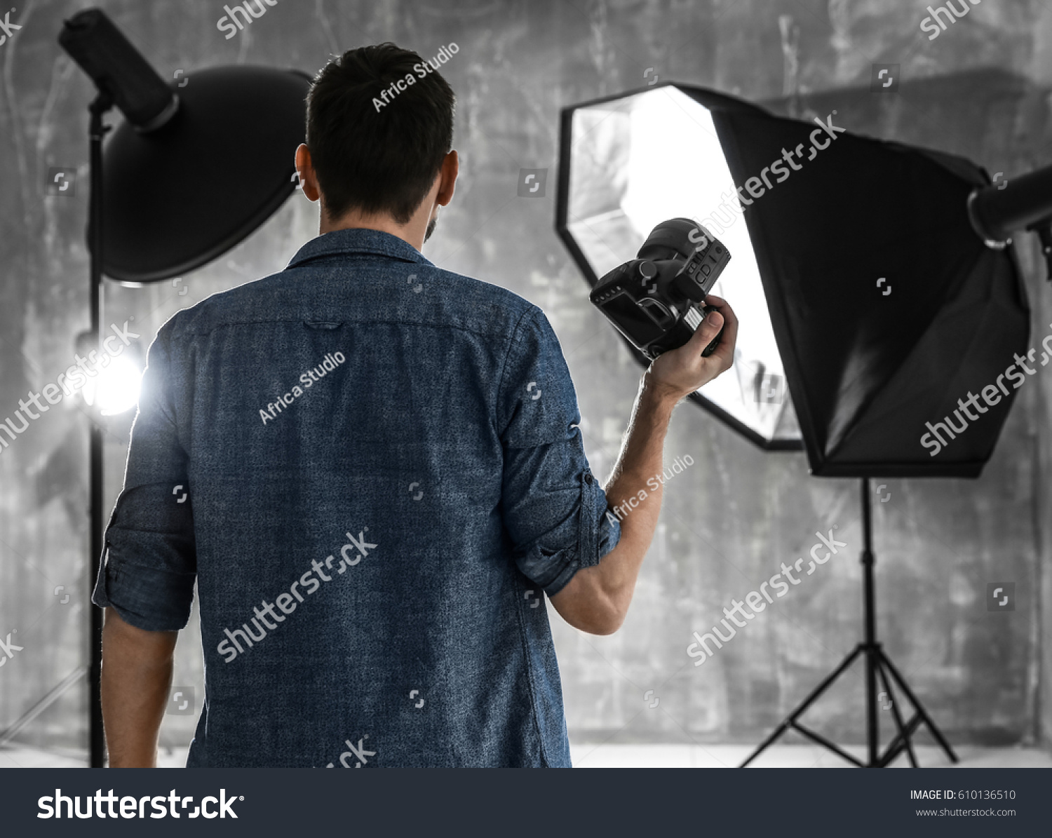 Young male photographer in studio with professional lighting equipment & Young Male Photographer Studio Professional Lighting Stock Photo ... azcodes.com