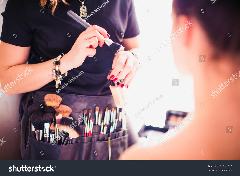 Makeup artist doing makeup for girl indoor #610155797