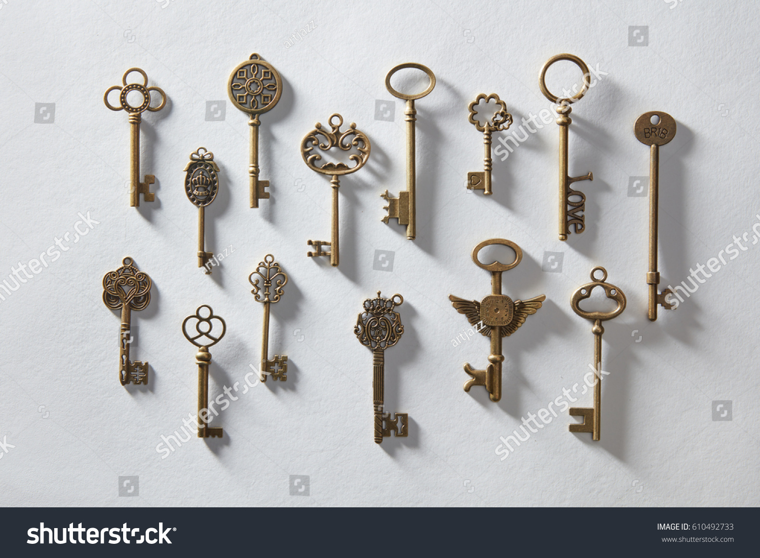 Vintage or antique door keys on white paper - Vintage Antique Door Keys On White Stock Photo 610492733