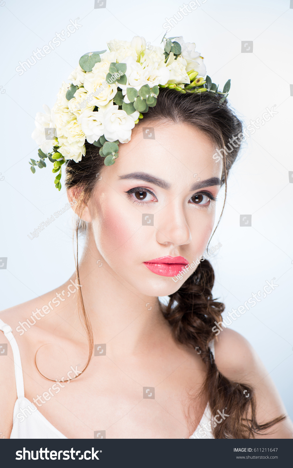 Portrait Of Serious Woman With Flowers In Hair Isolated On White