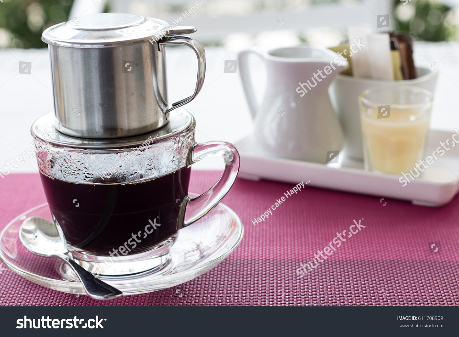 A clear cup of coffee with silver filter and served with milk and sugar background #611708909