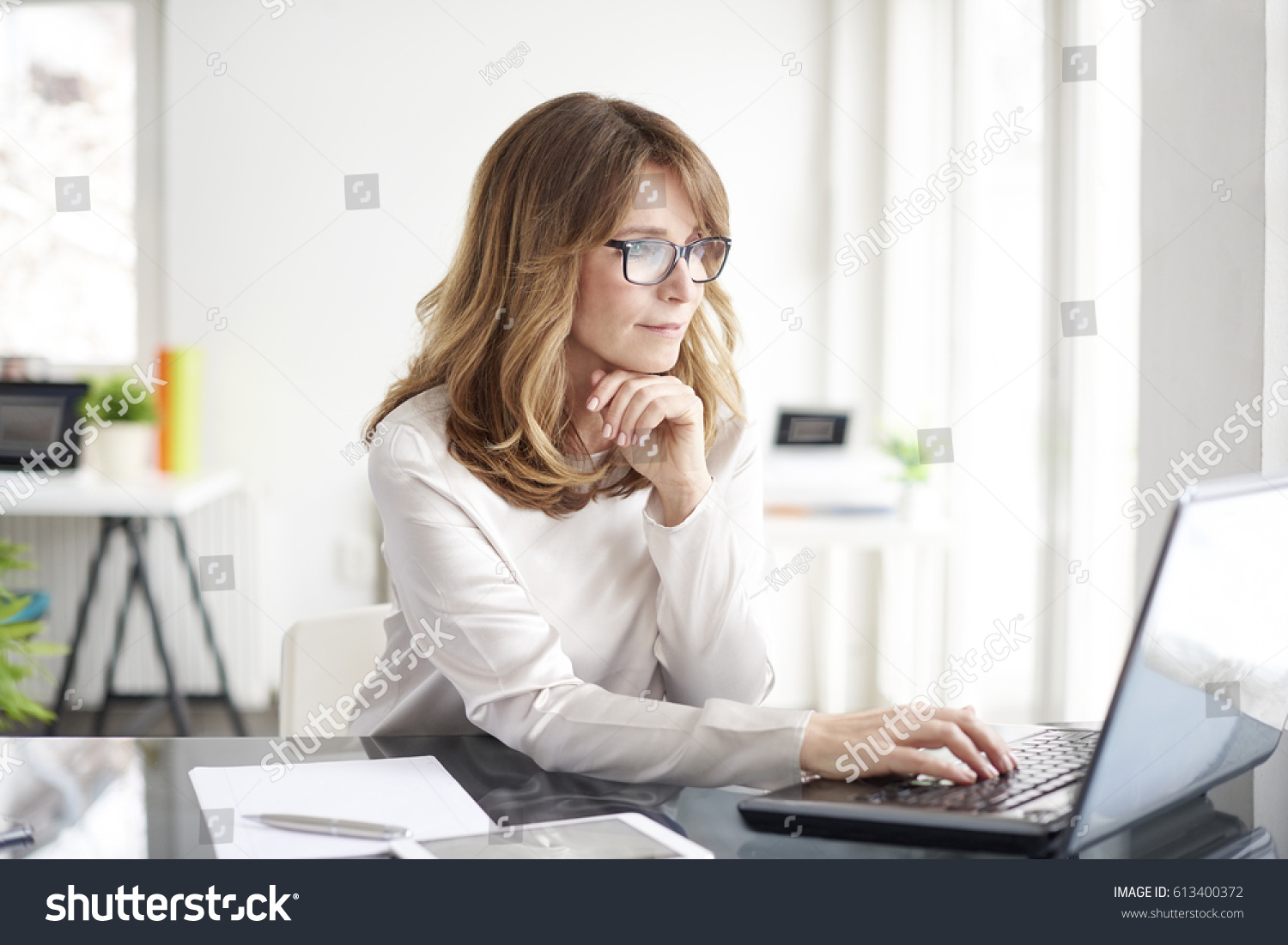 Shot of an attractive mature businesswoman working on laptop in her workstation. #613400372
