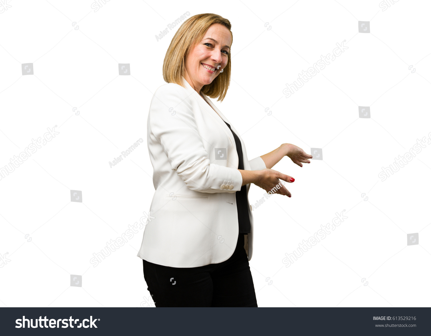 blonde mature woman doing welcome gesture stock photo (royalty free