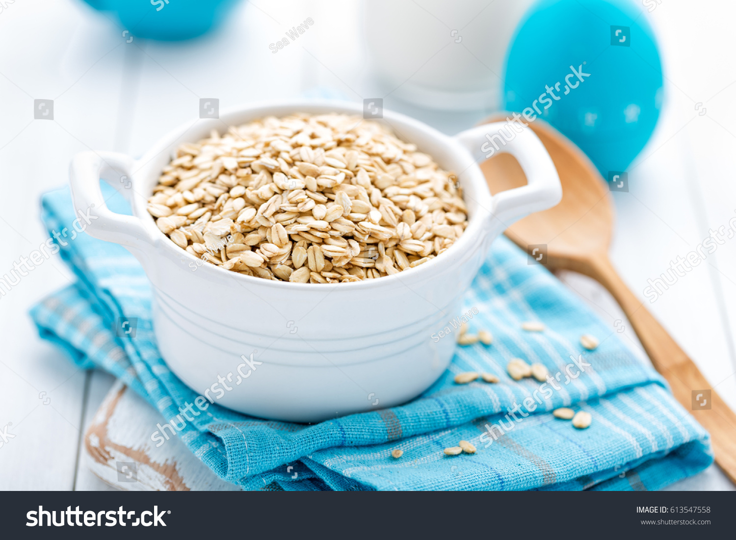 Rolled oats on white wooden background #613547558