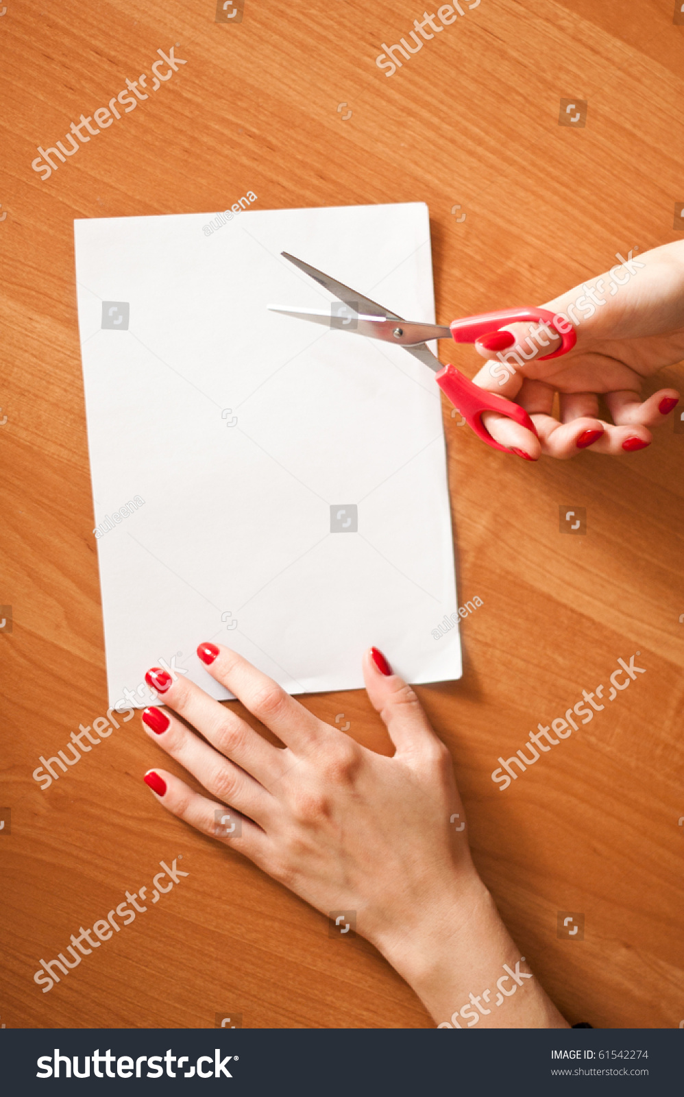 Cutting A Piece Of Paper : Hands cutting a piece of paper stock photo