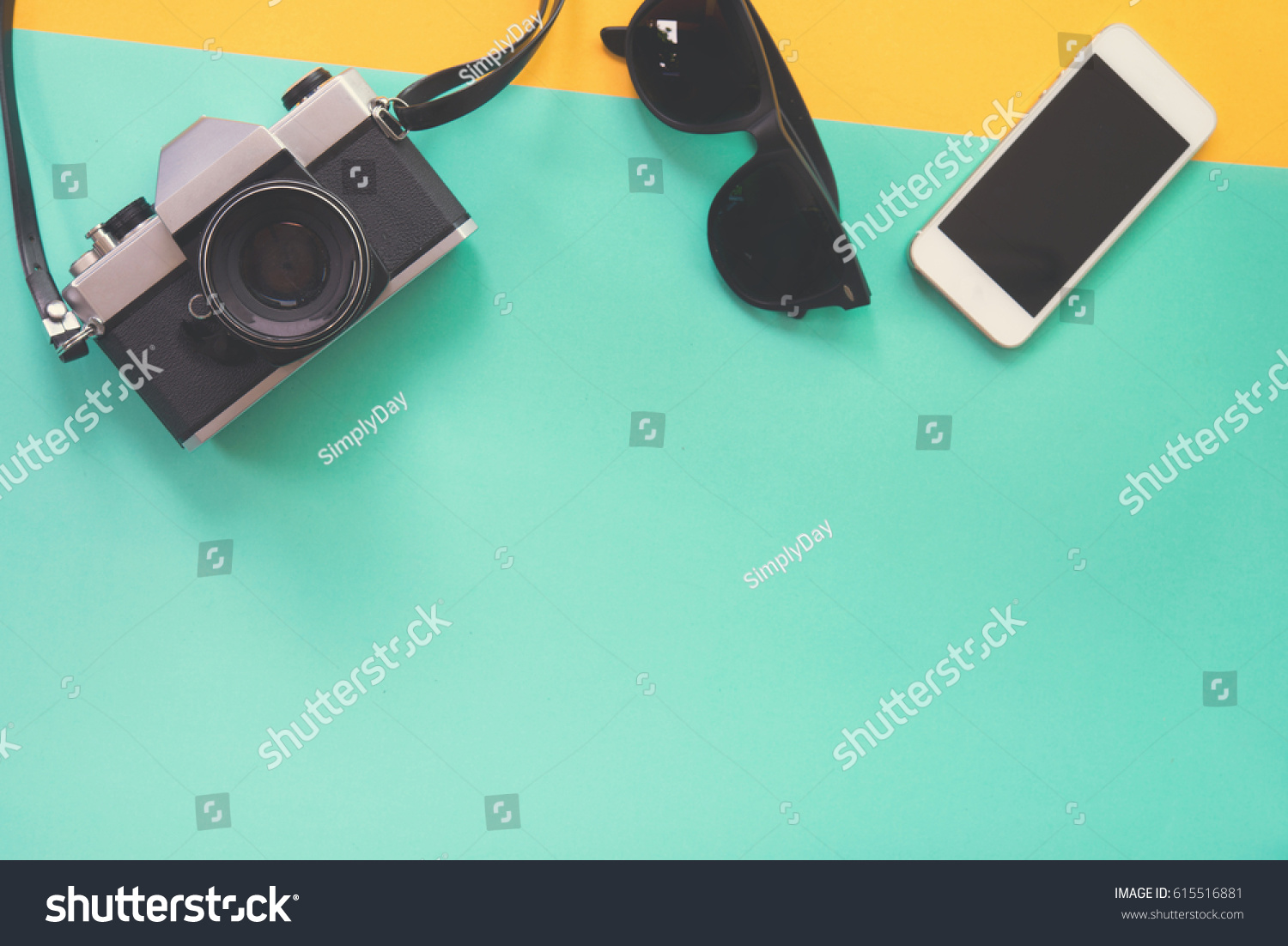 d1a33967fb1f Flat lay design of work desk with sunglasses old camera and smartphone on  green and yellow