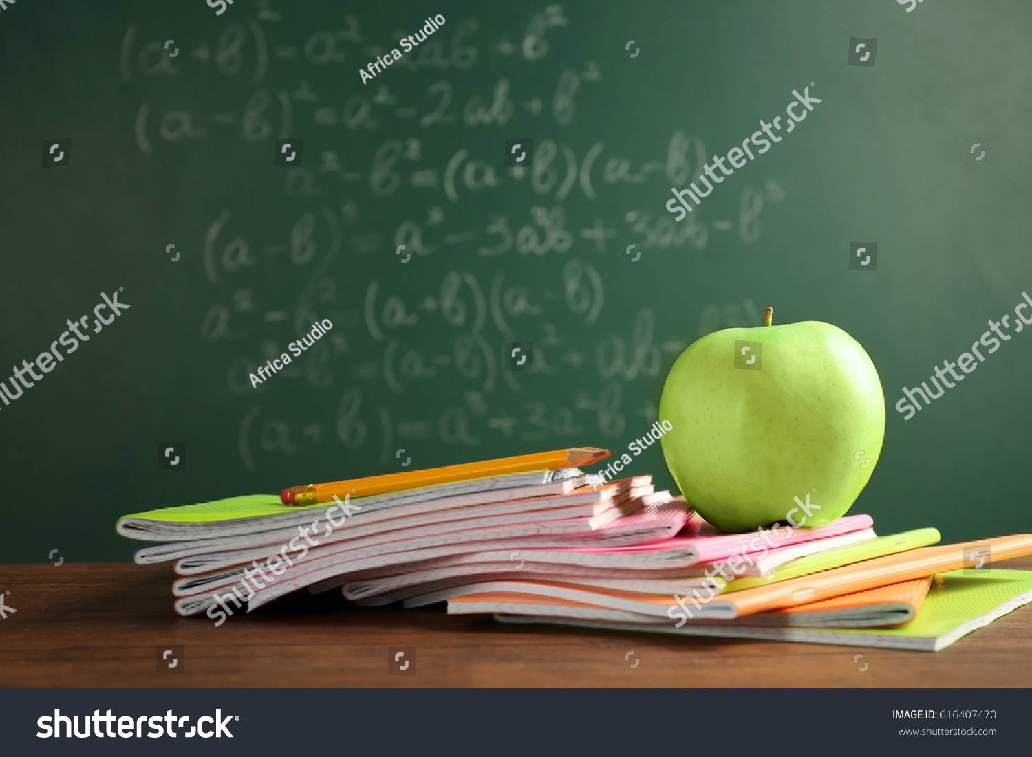 Copybooks And Apple On Chalkboard Background