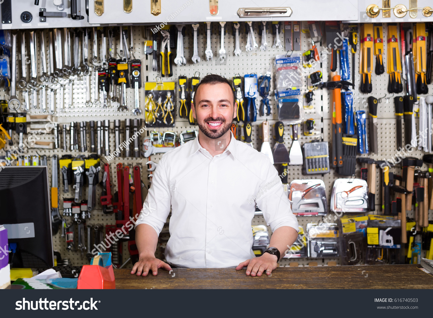 Portrait Of Young Cheerful American Man At The Cash Desk Working In  Tool Ware Shop