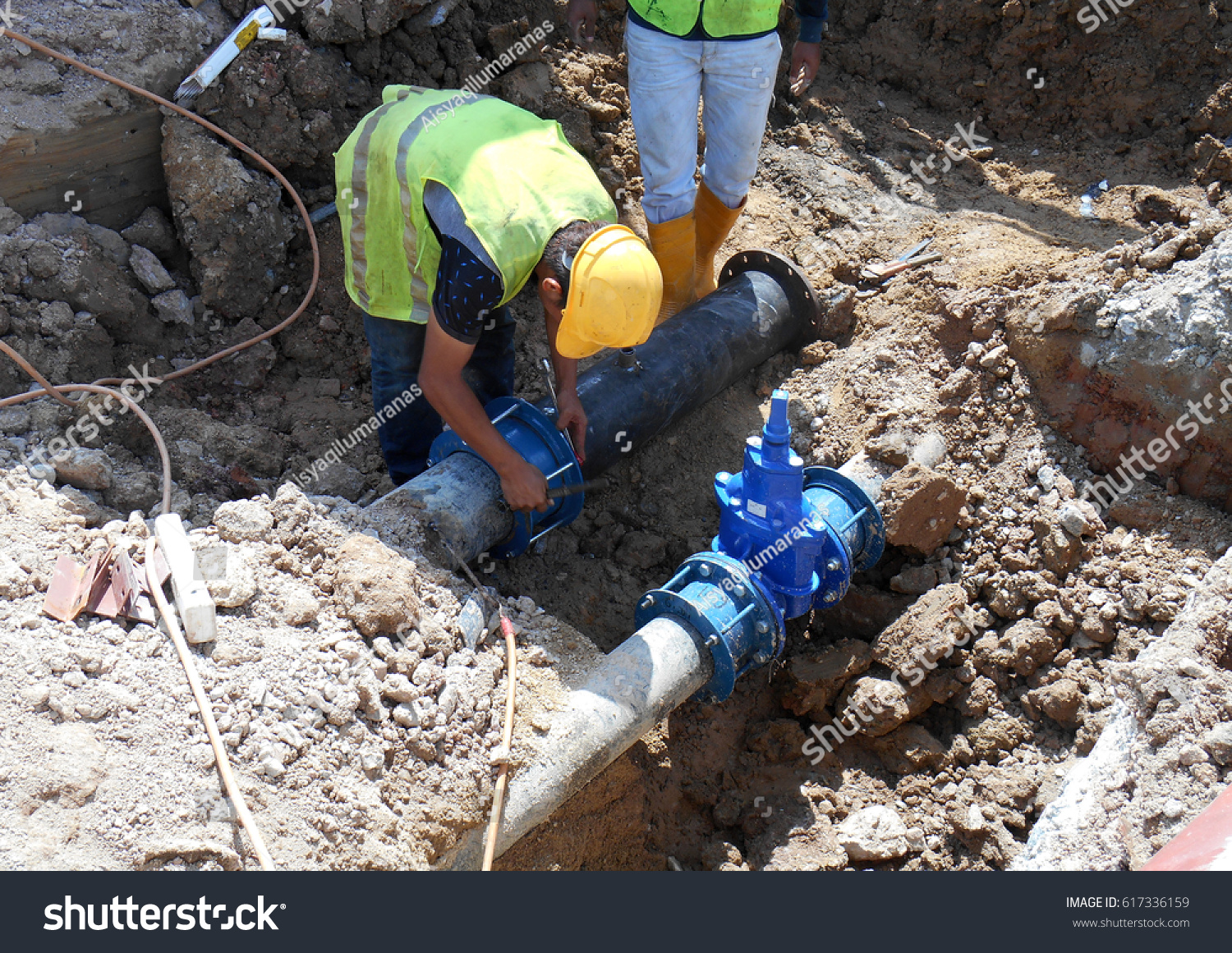 Construction workers install underground utility services
