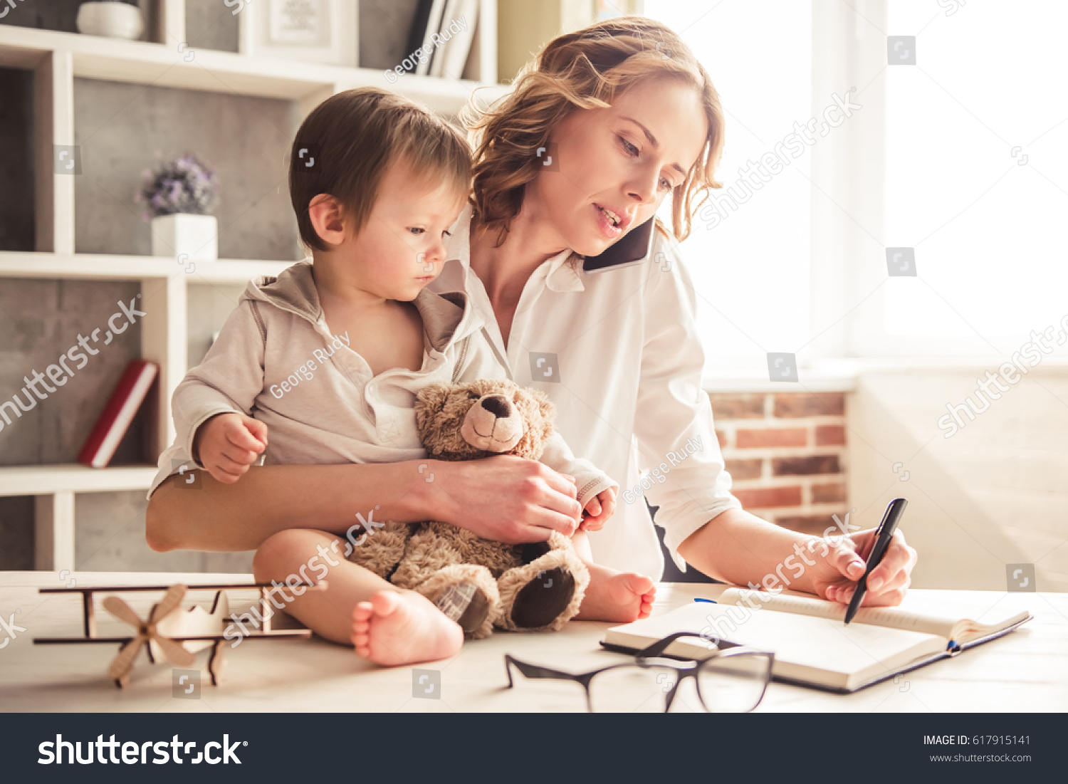Beautiful business mom is talking on the mobile phone and taking notes while spending time with her cute baby boy at home #617915141