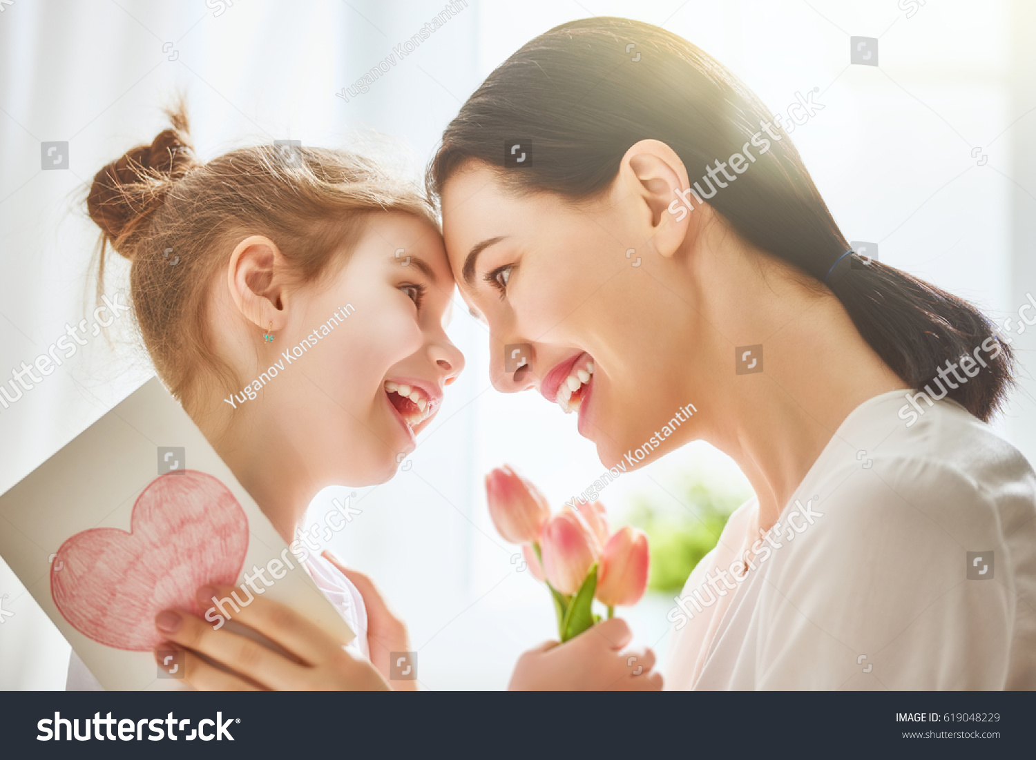 Happy mother's day! Child daughter congratulates mom and gives her flowers tulips and postcard. Mum and girl smiling and hugging. Family holiday and togetherness. #619048229