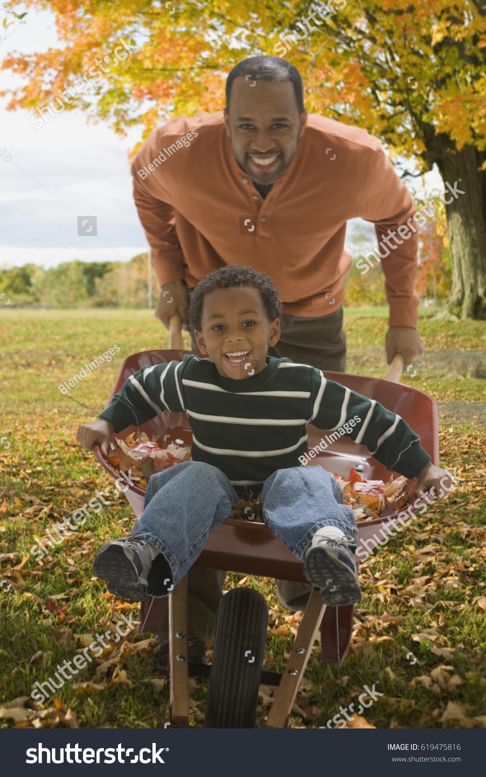 African Father Pushing Son Wheelbarrow Autumn Stock Photo