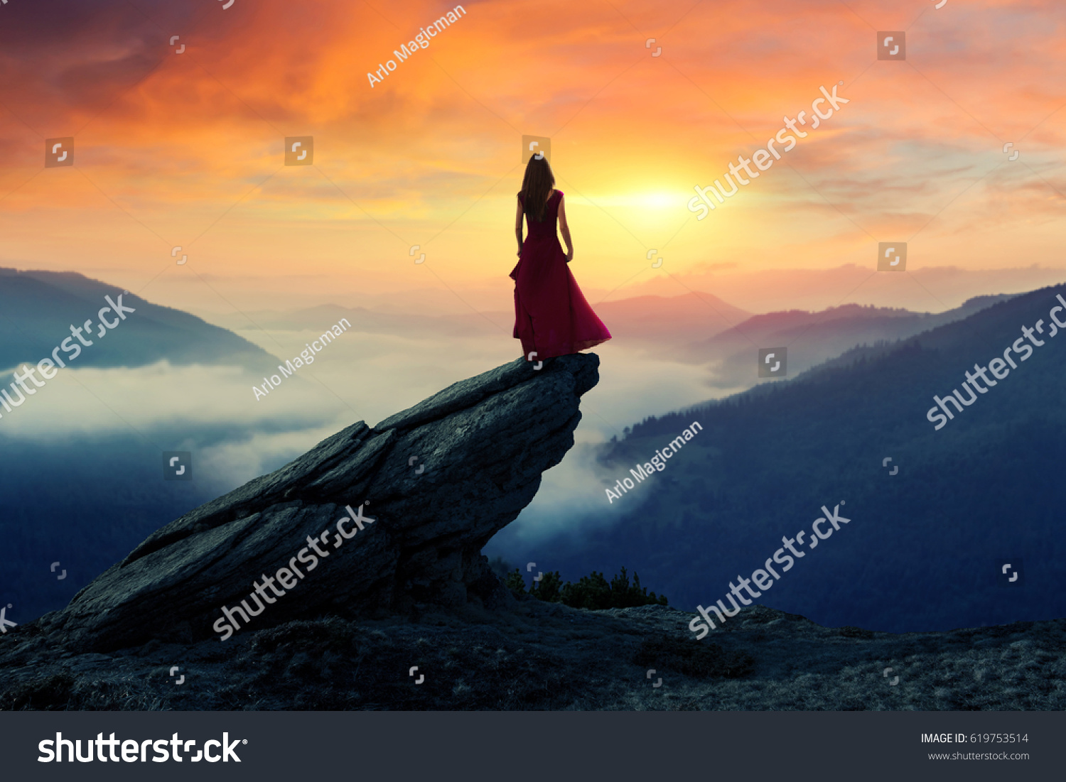 Fine art of a women standing alone on the top of a cliff in front of