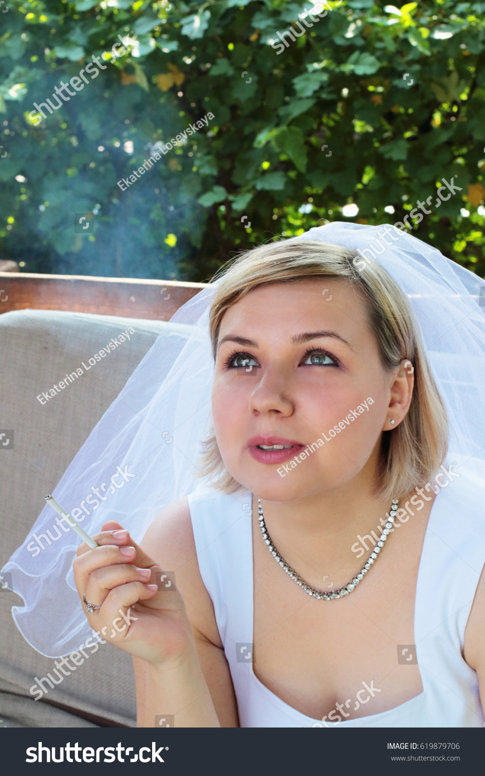 Young Nervous Sad Bride In A White Wedding Dress Smoking Cigarette Outdoors Against Background: Smoking Brides Wedding Dress At Websimilar.org