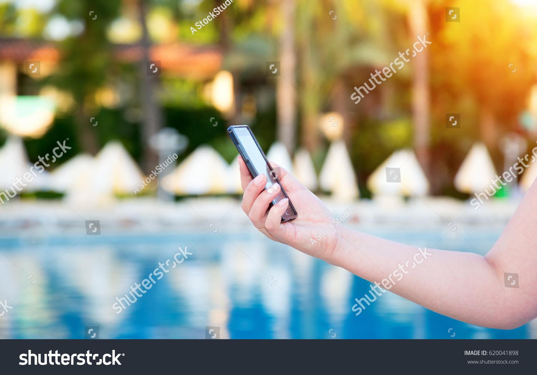 Closeup Female Hand Holds Phone Against Stock Photo (Edit ...