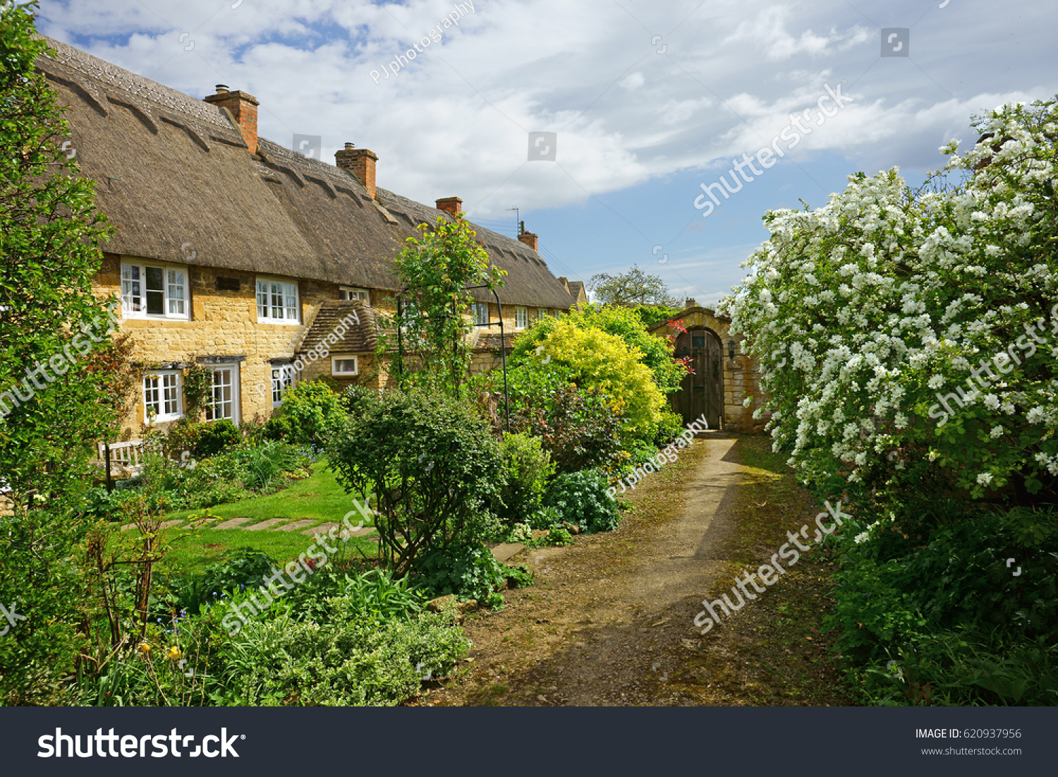A Row Of Pretty Thatched Cottages And Gardens In Spring The Cotswold Town Chipping