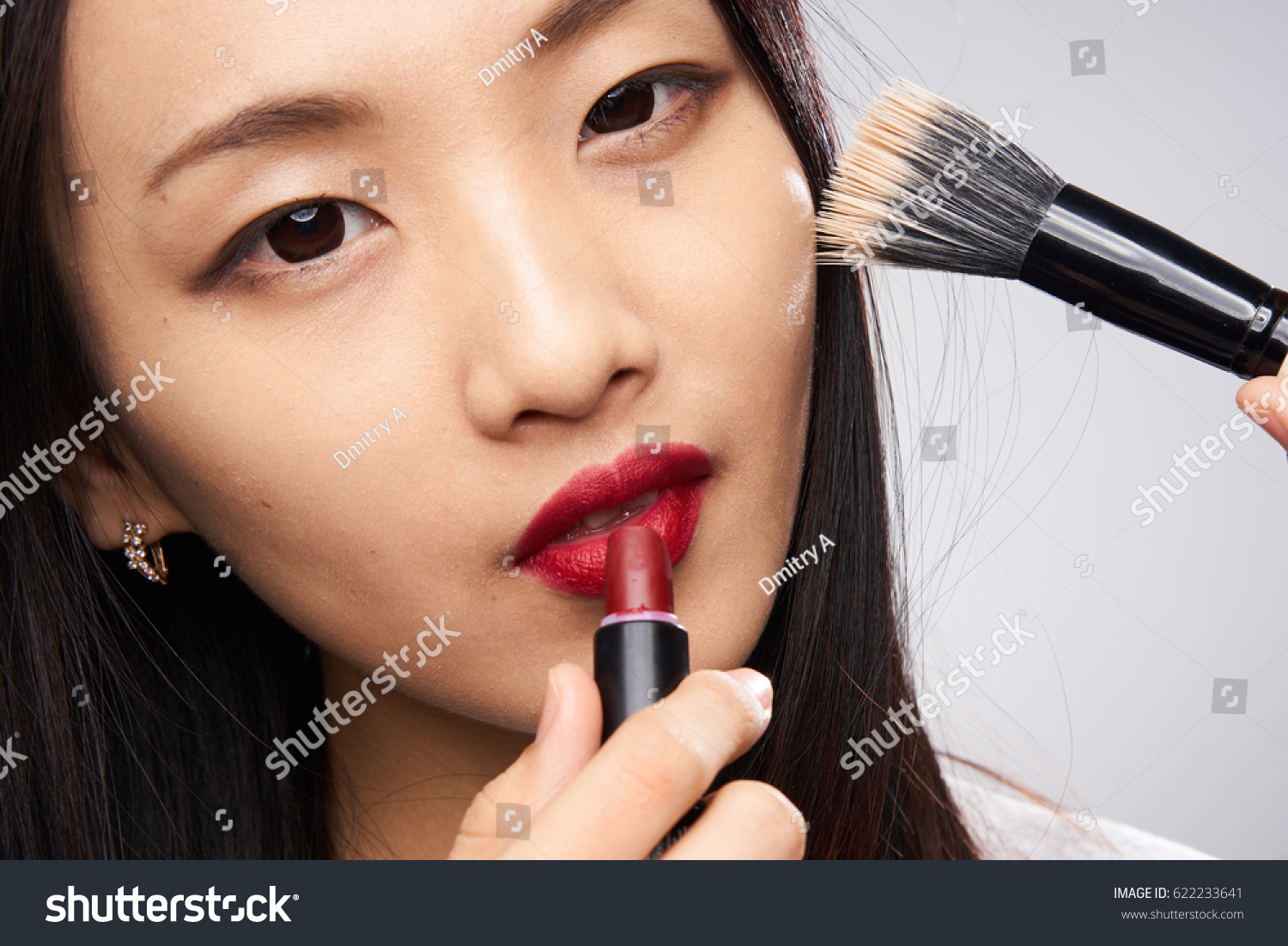 Asian woman on white background red lips makeup brush