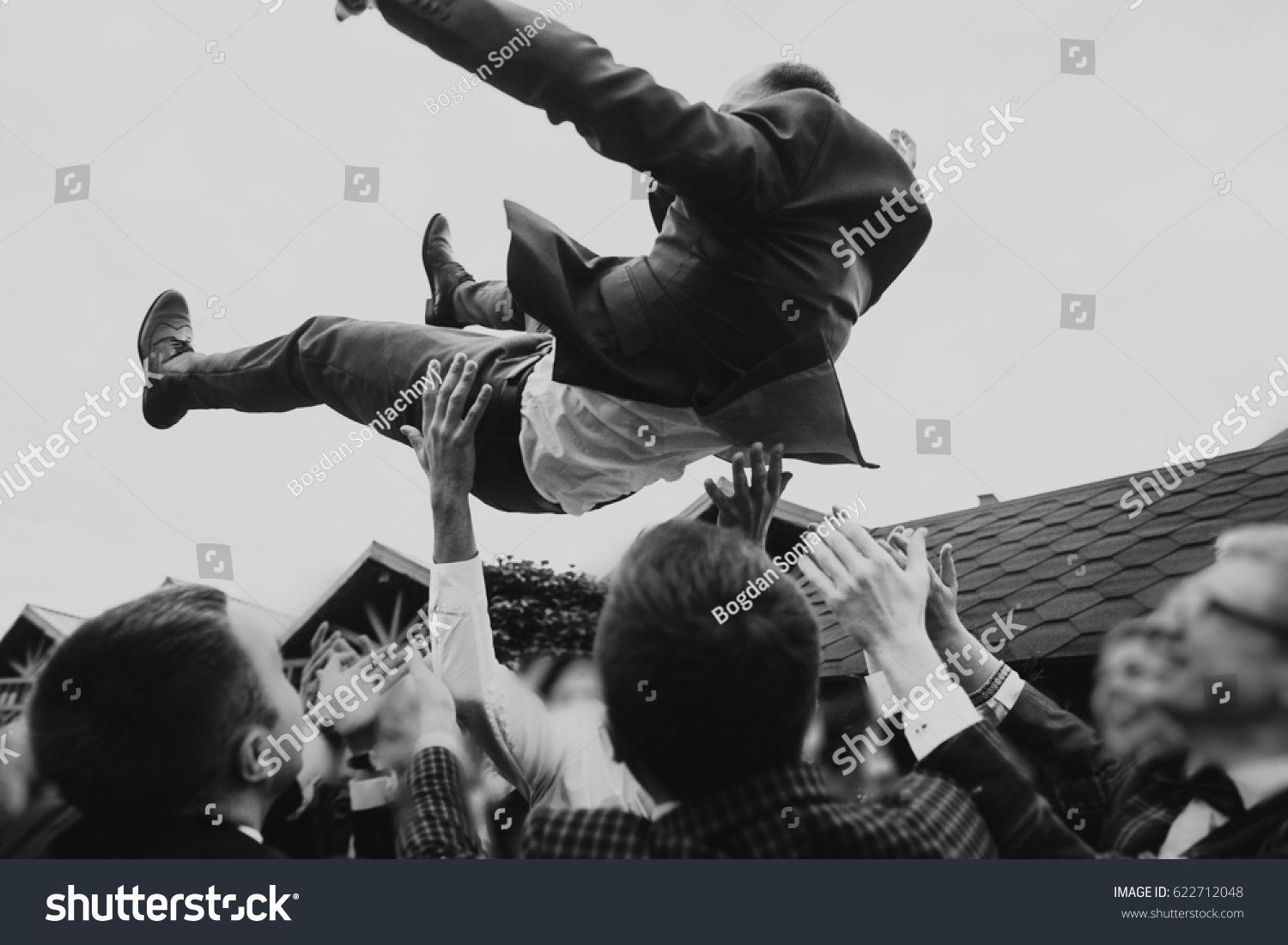 men tossing up groom at stylish wedding reception. groomsmen having fun and throwing up in air. emotional funny moment, space for text. joyful friends. black white photo #622712048