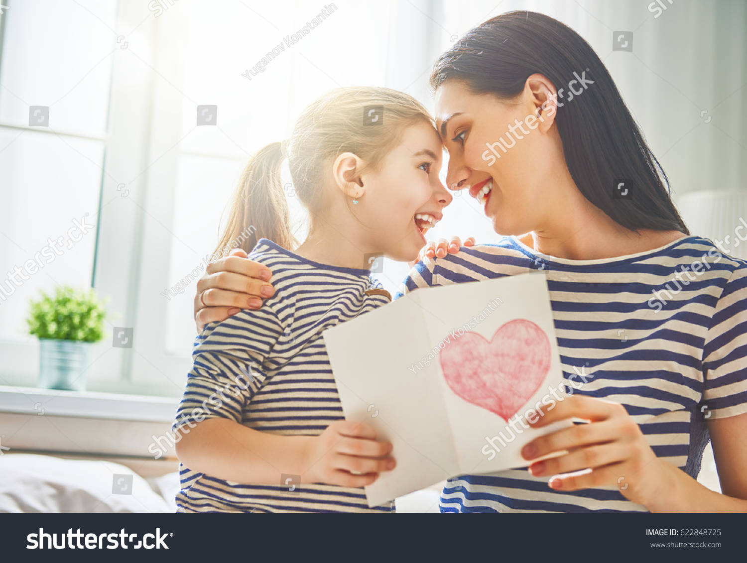 Happy mother's day! Child daughter congratulates mom and gives her postcard. Mum and girl smiling and hugging. Family holiday and togetherness. #622848725