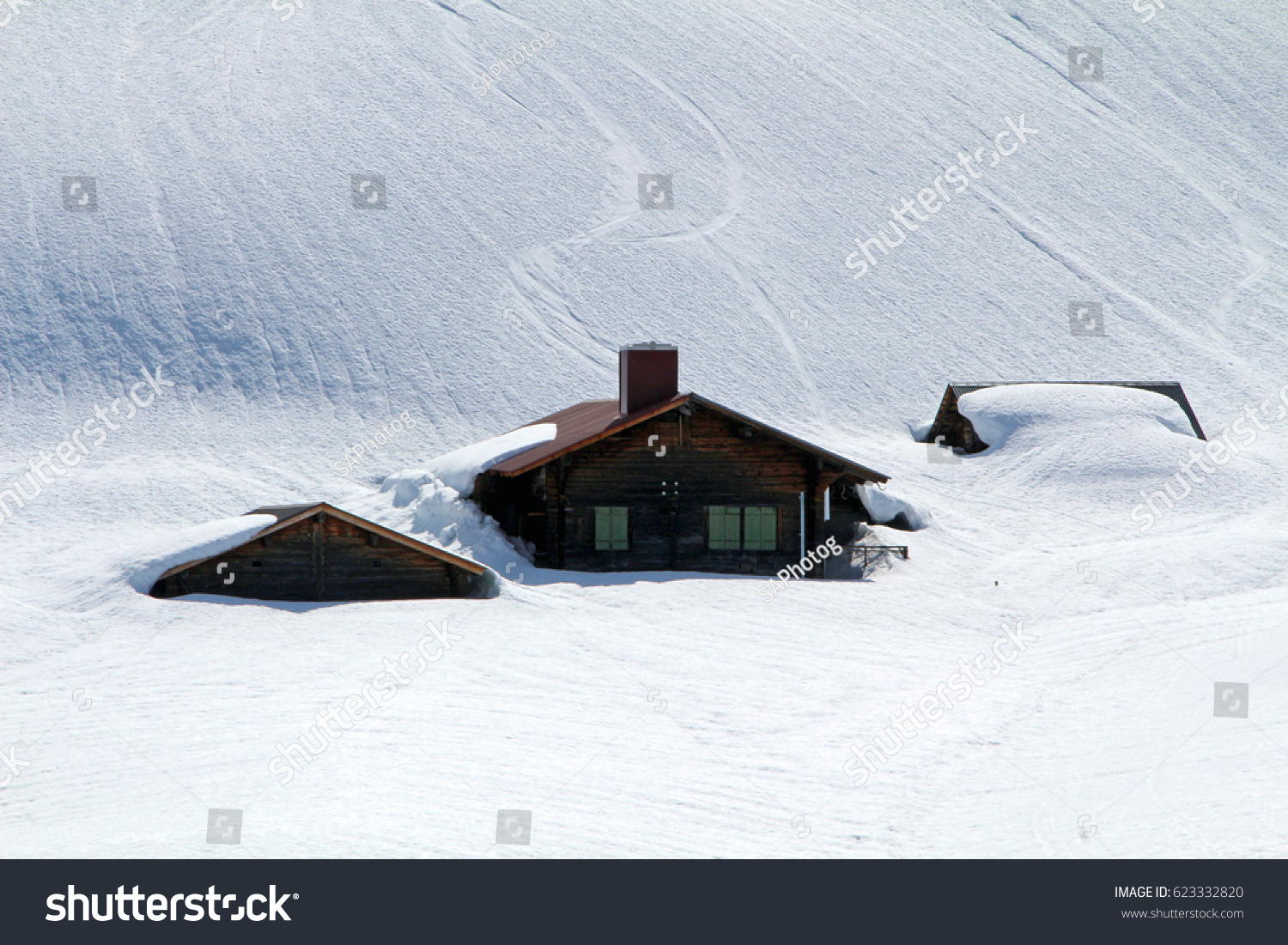 Wooden Chalets And Cabins Buried Under Snow On A Ski Resort In The Swiss Alps