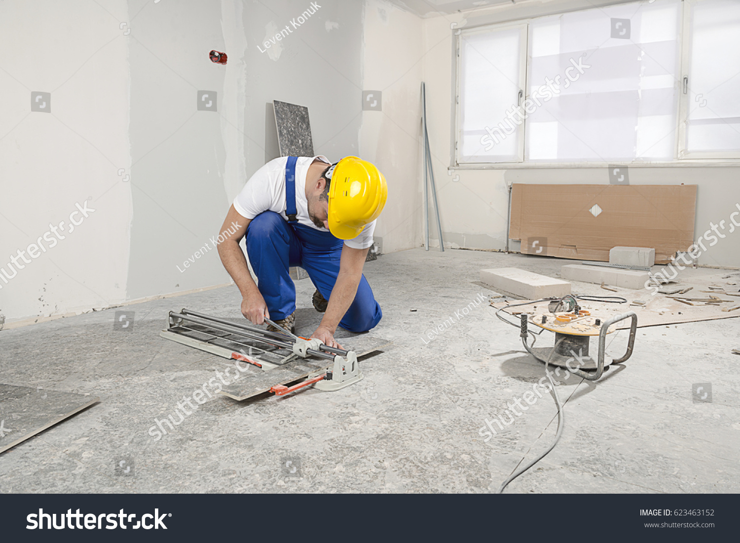 Construction worker wearing bib overalls hard stock photo construction worker wearing bib overalls and hard hat cutting ceramic tiles using ceramic cutter dailygadgetfo Images