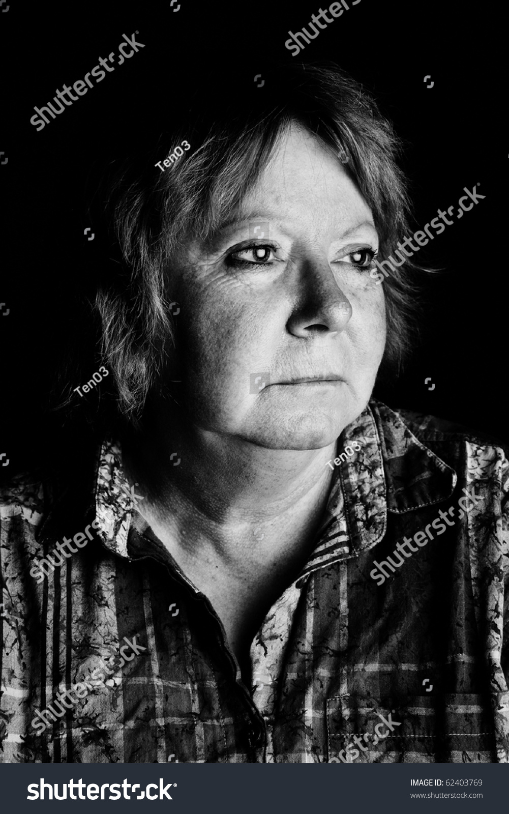 A black and white low key portrait of a woman in her fifties