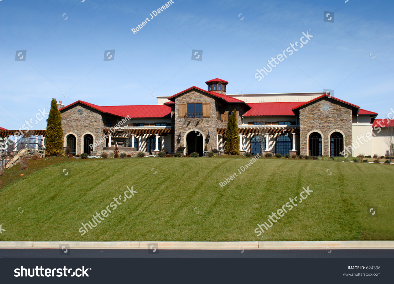 Large stone house with red tile roof under blue skies