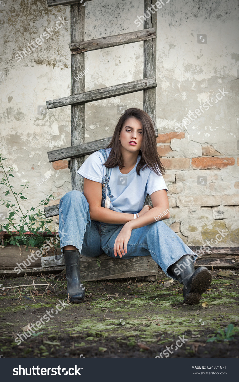 Beautiful Young Woman Is Sitting On The Ladder Leaning On The Old Rustic Wall
