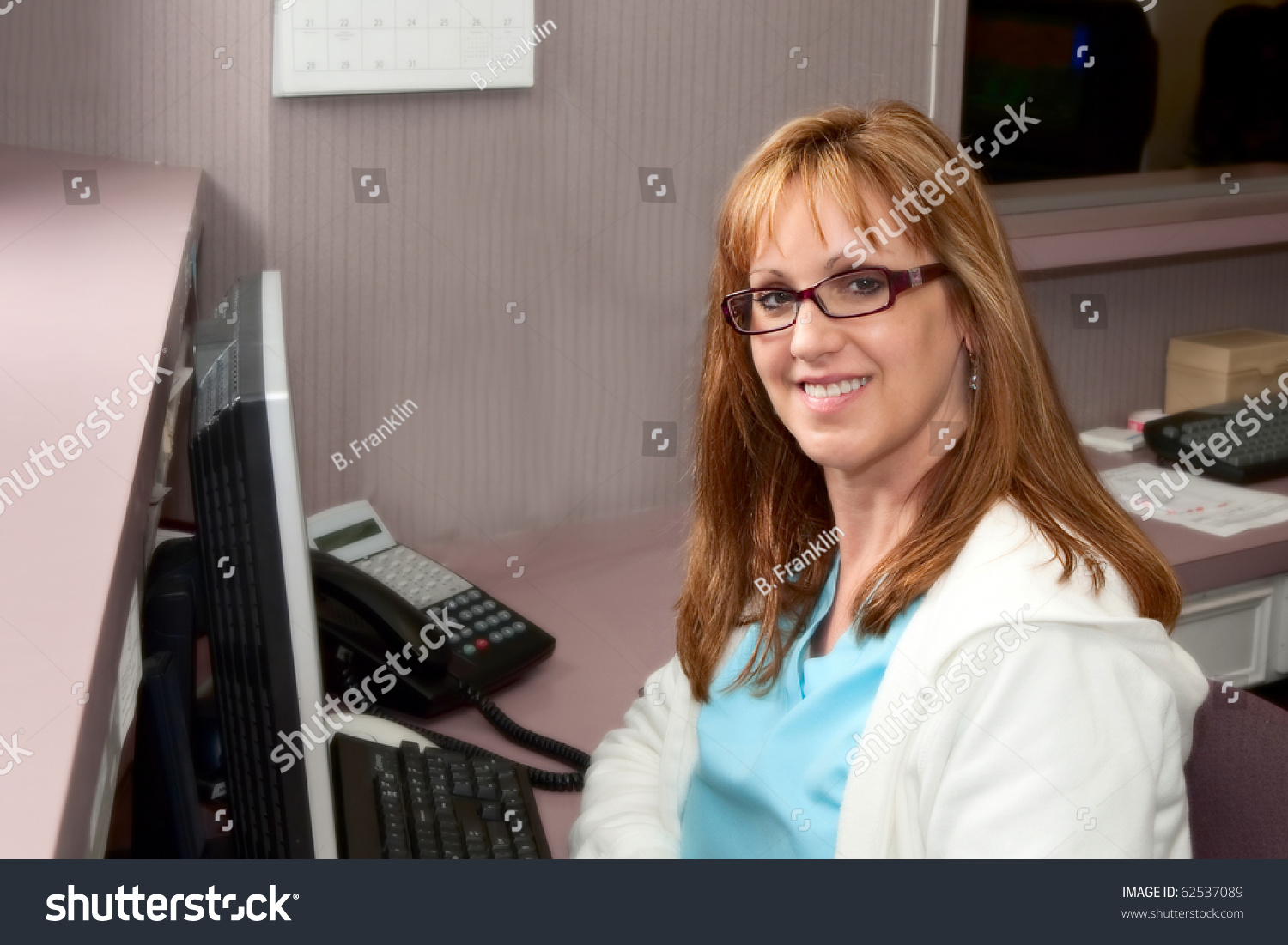 Pretty receptionist doctors office sitting front stock photo pretty receptionist in doctors office sitting in front of computer sciox Images