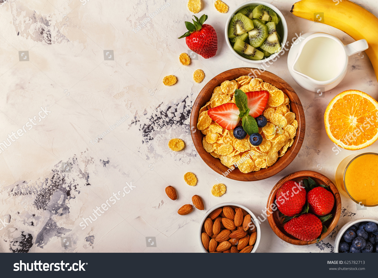 Healthy breakfast - bowl of corn flakes, berries and fruit, nuts, orange juice, milk, top view. #625782713