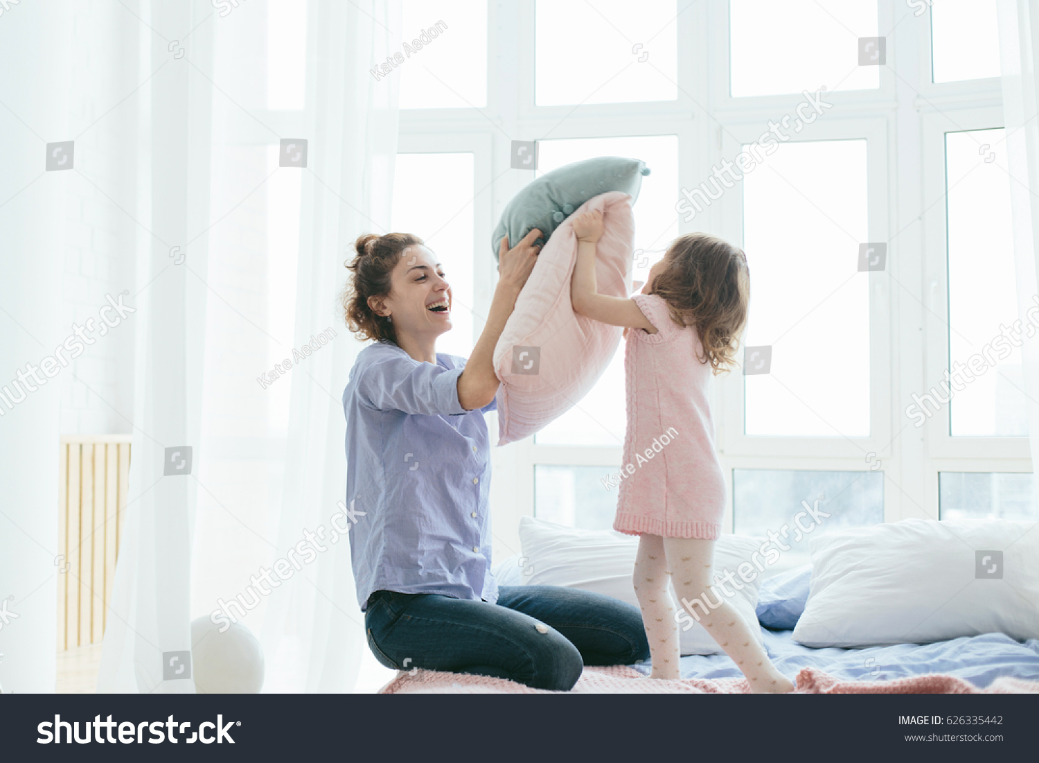Young mother and her little daughter playing with cushions on bed. Funny pillow fight. Soft pastel colors, pink and blue. Selective focus. Play together and enjoy the moment! Family time on weekend.  #626335442