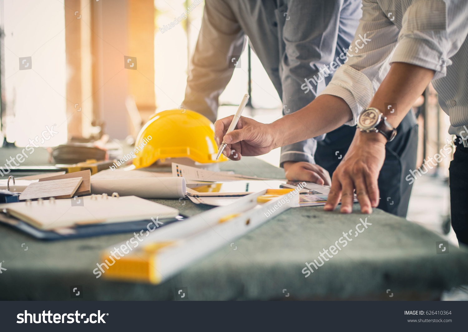 Two business man construction site engineer. Engineering objects on workplace with partners interacting on background #626410364