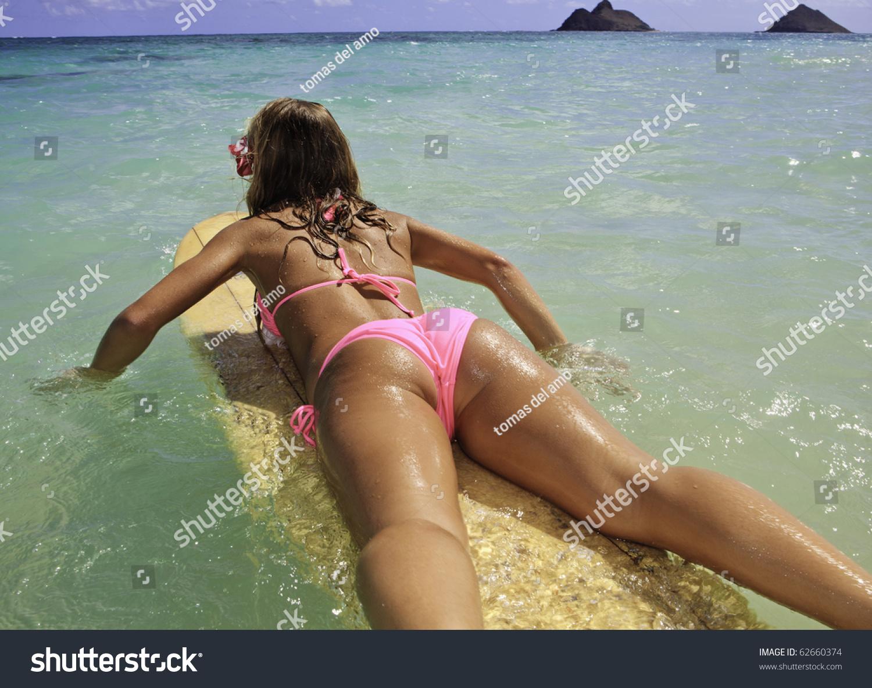 Little girl in bikini rear view rear view of a teenage girl in pink bikini at the beach in hawaii paddling  her