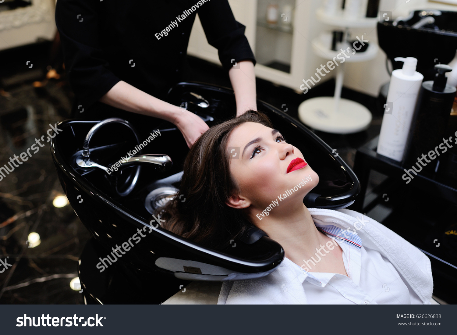 Beautiful young girl washing her head in a beauty salon #626626838