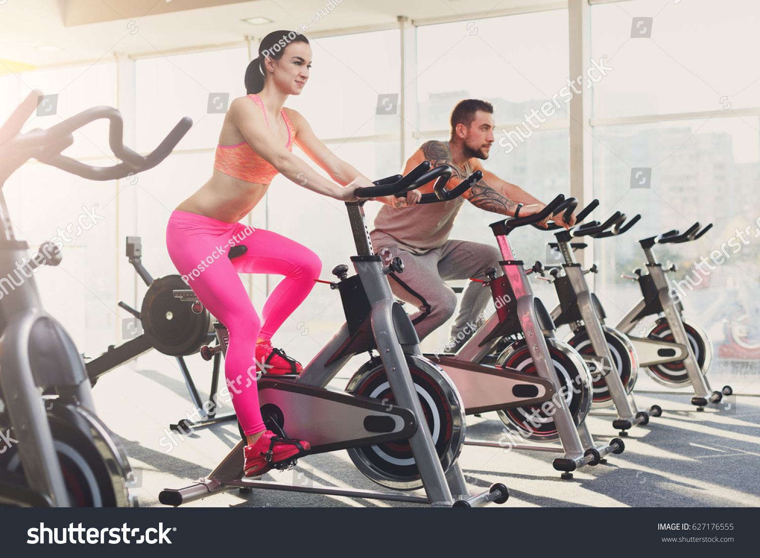 Young Happy Couple In Fitness Club Cardio Workout On Stationery Exercise Bikes Healthy Lifestyle