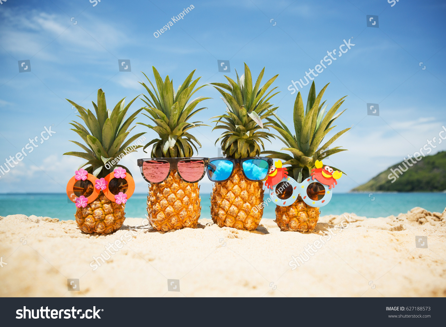 Family of funny attractive pineapples in stylish sunglasses on the sand against turquoise sea. Tropical summer vacation concept. Happy sunny day on the beach of tropical island. Family holiday #627188573