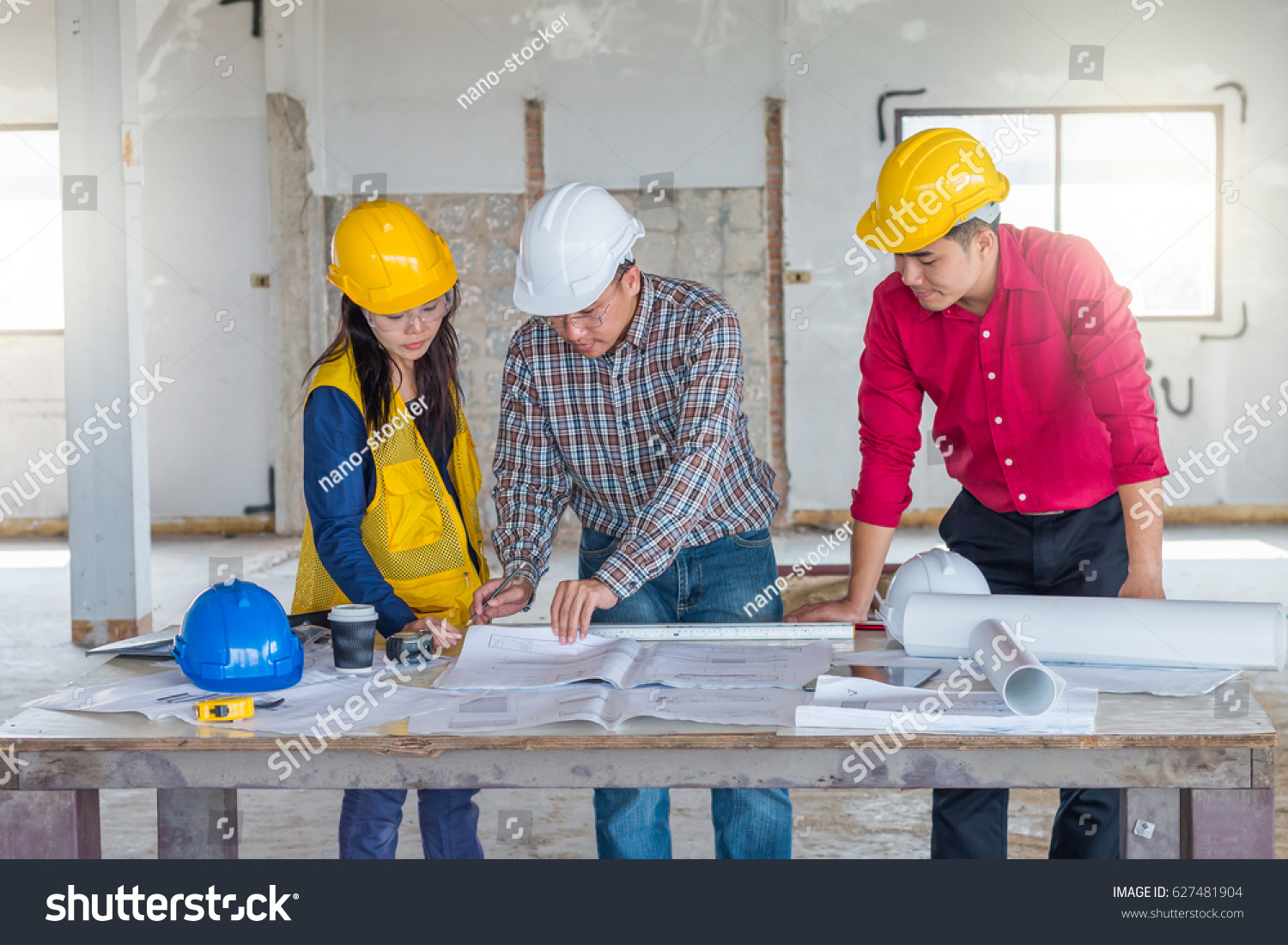 Group engineer checking blueprint on table stock photo 627481904 group of engineer checking the blueprint on the table and talking about construction project with commitment malvernweather Gallery
