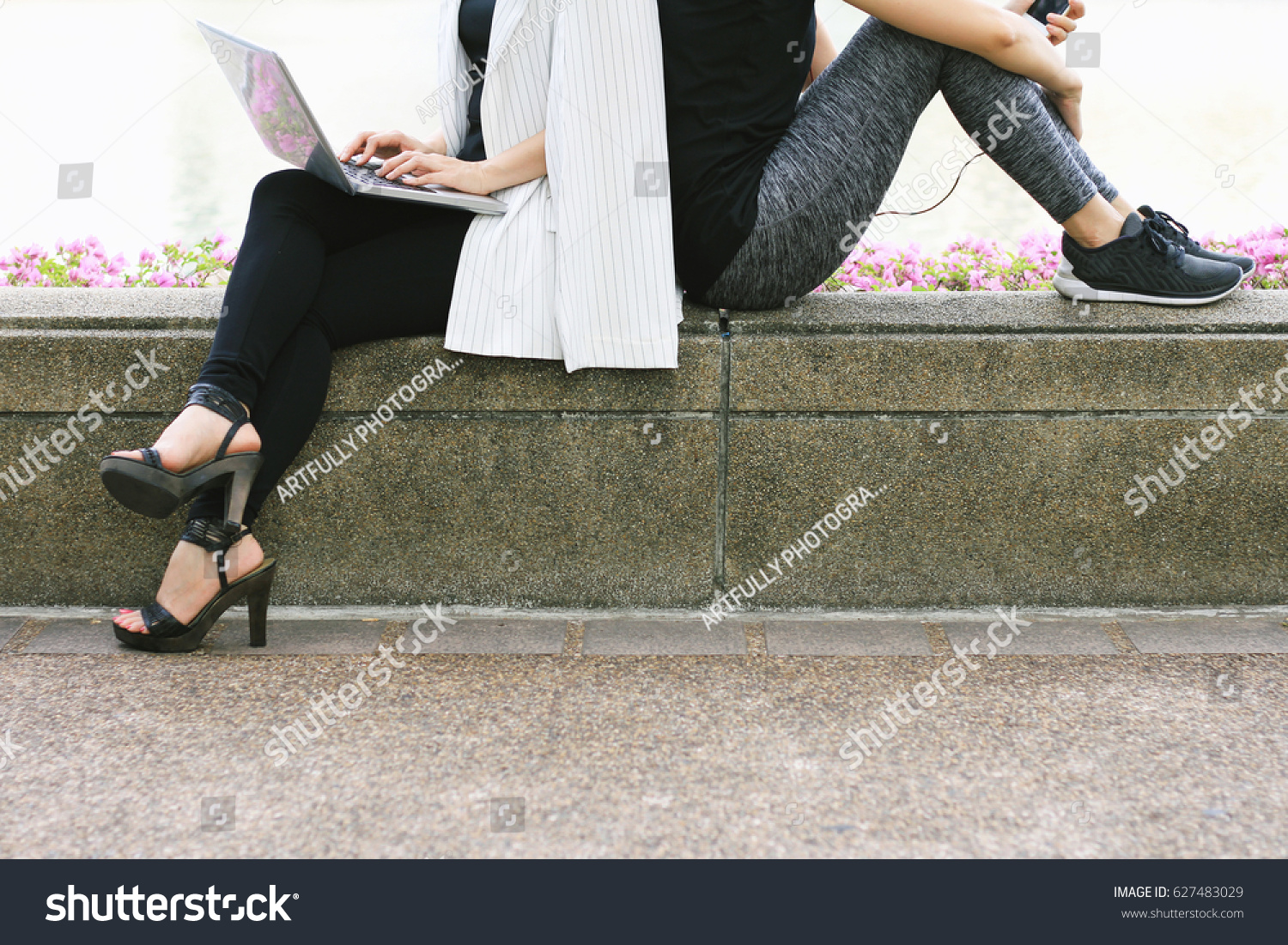 Business woman working on the laptop computer sitting near the relaxing sport woman in city park, Life balance concept, Workaholic and healthy lifestyle. #627483029