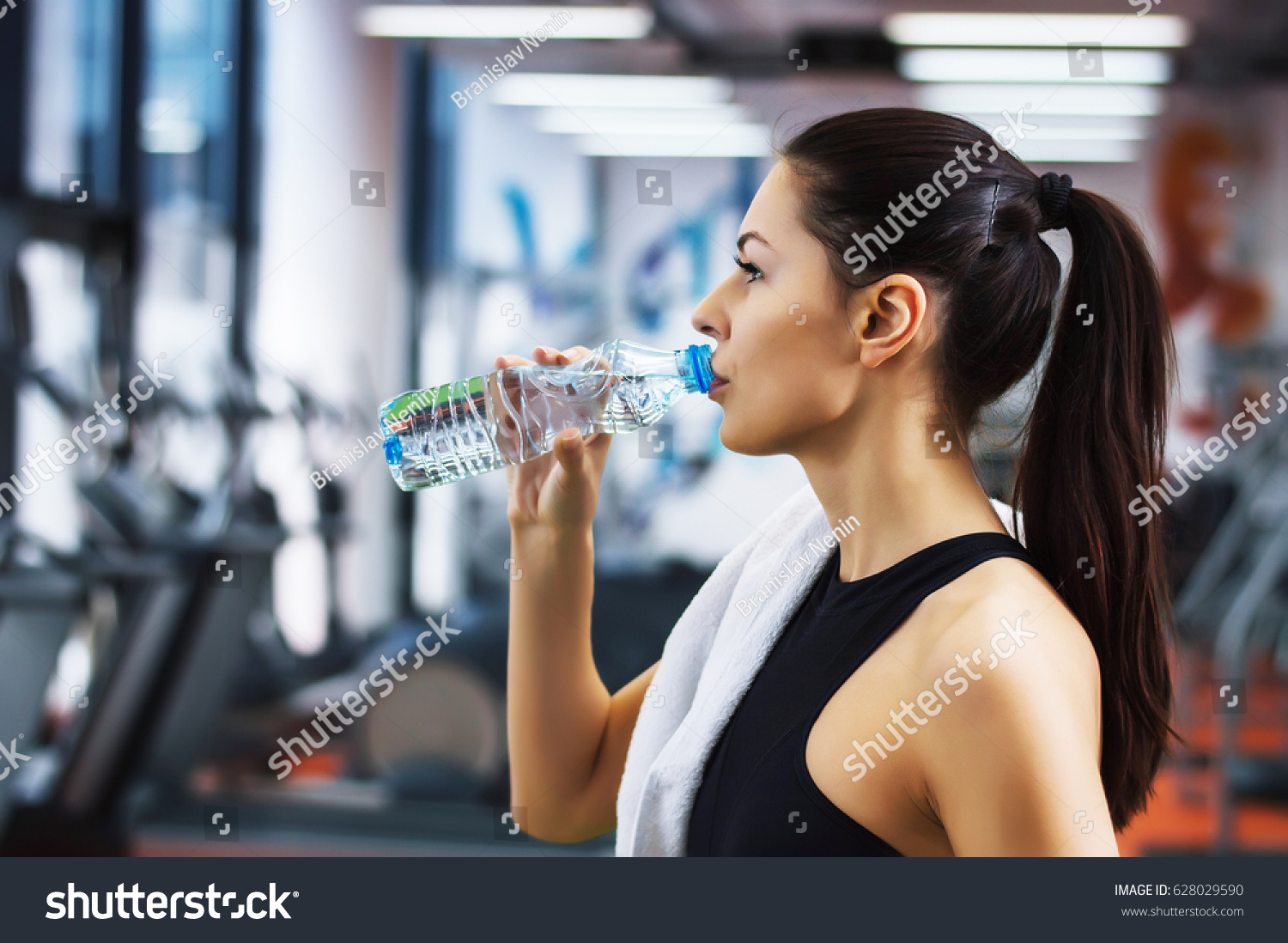 Young woman drinking water gym stock photo 628029590 shutterstock young woman drinking water in the gym sciox Gallery