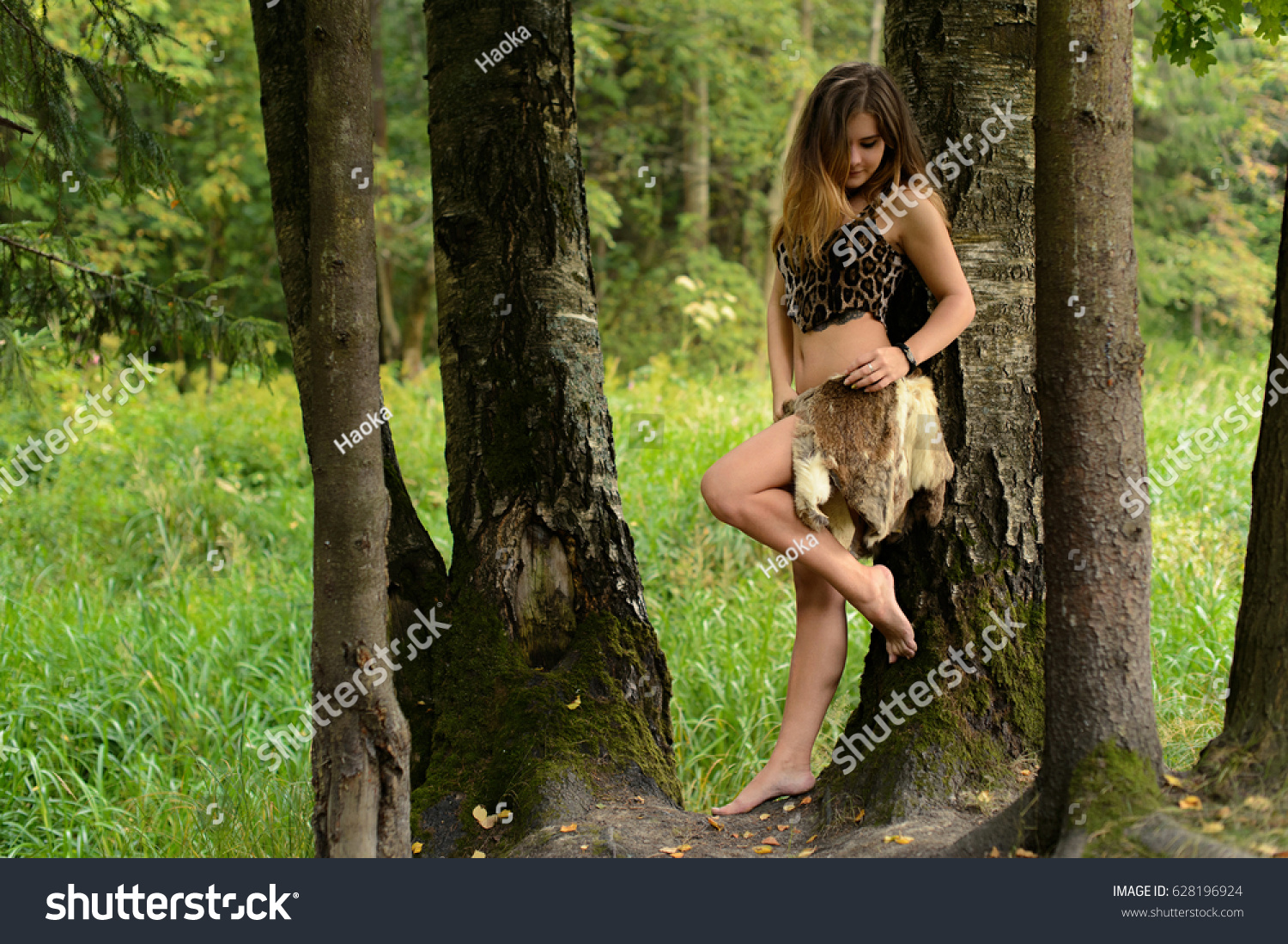 https://image.shutterstock.com/z/stock-photo-young-girl-hunter-in-furs-in-a-forest-leaned-against-a-tree-628196924.jpg