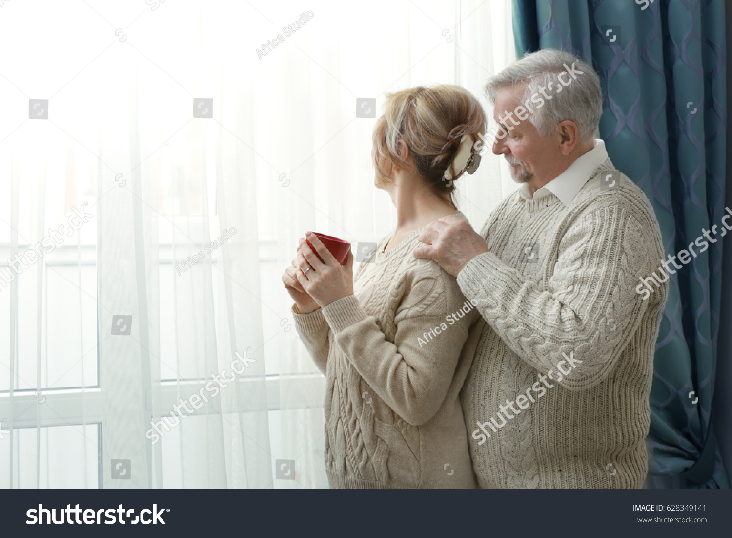 Cute elderly couple near window at home #628349141