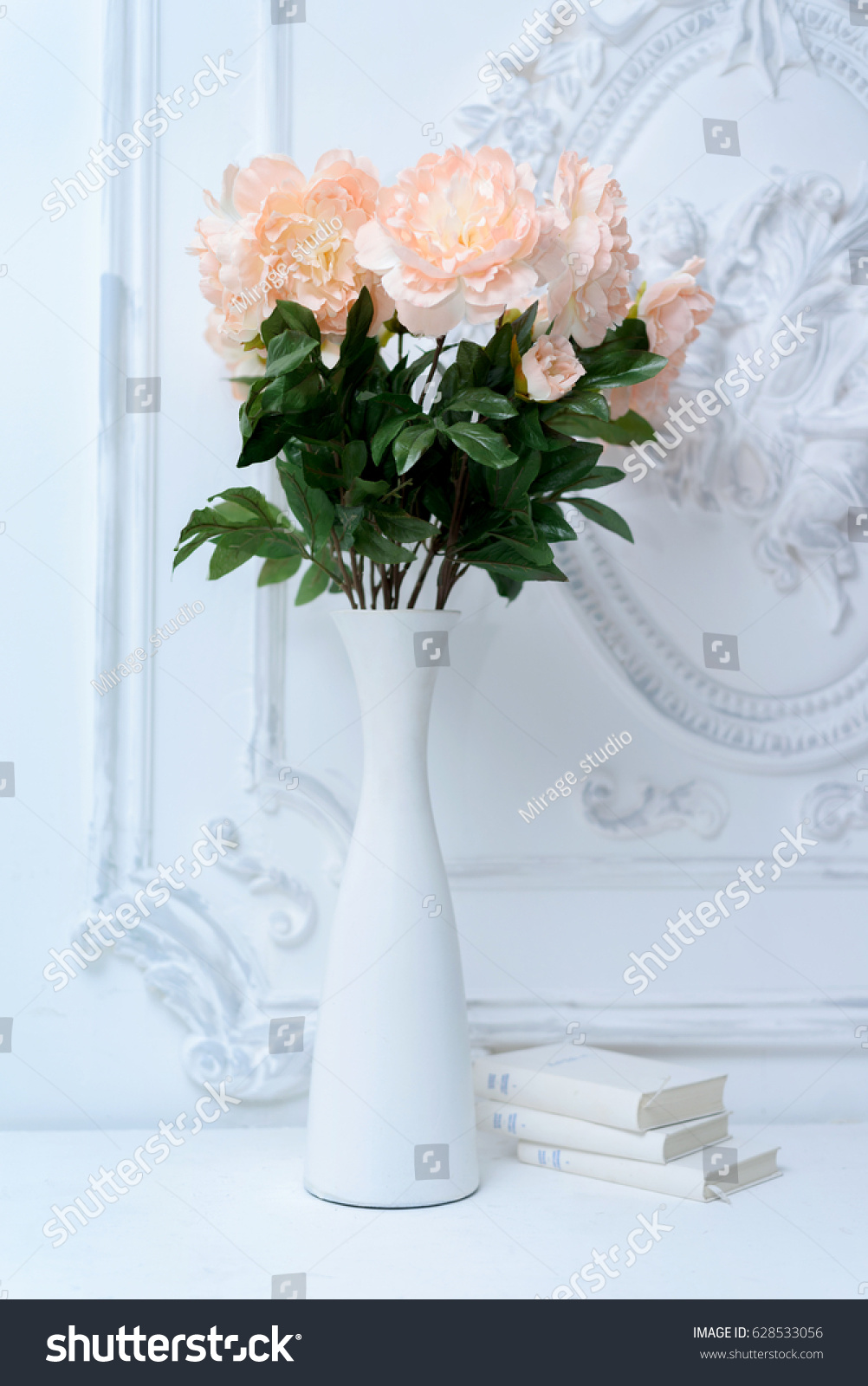 Artificial pink peonies white vase next stock photo 628533056 artificial pink peonies in a white vase next to white books composition of flowers in reviewsmspy