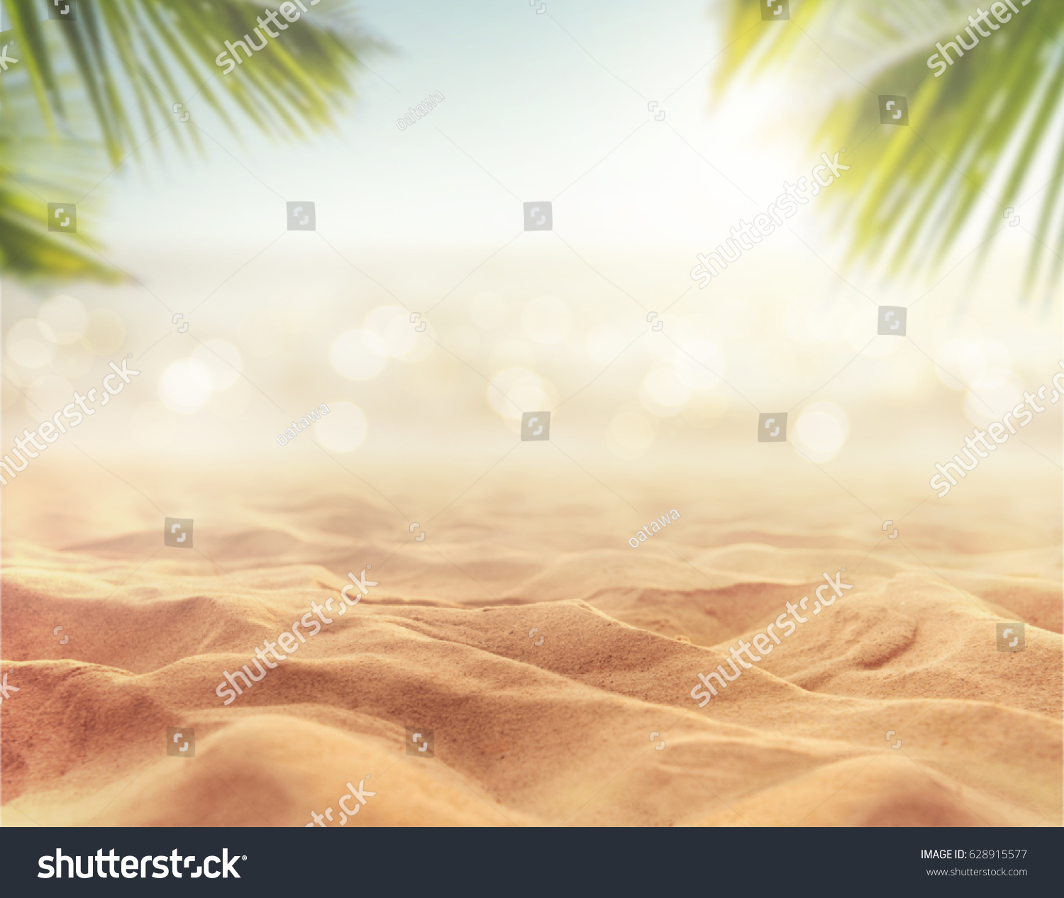 Background Of Blurred Beach And Sea Waves With Bokeh: Sand Blurred Palm Tropical Beach Bokeh Stock Photo