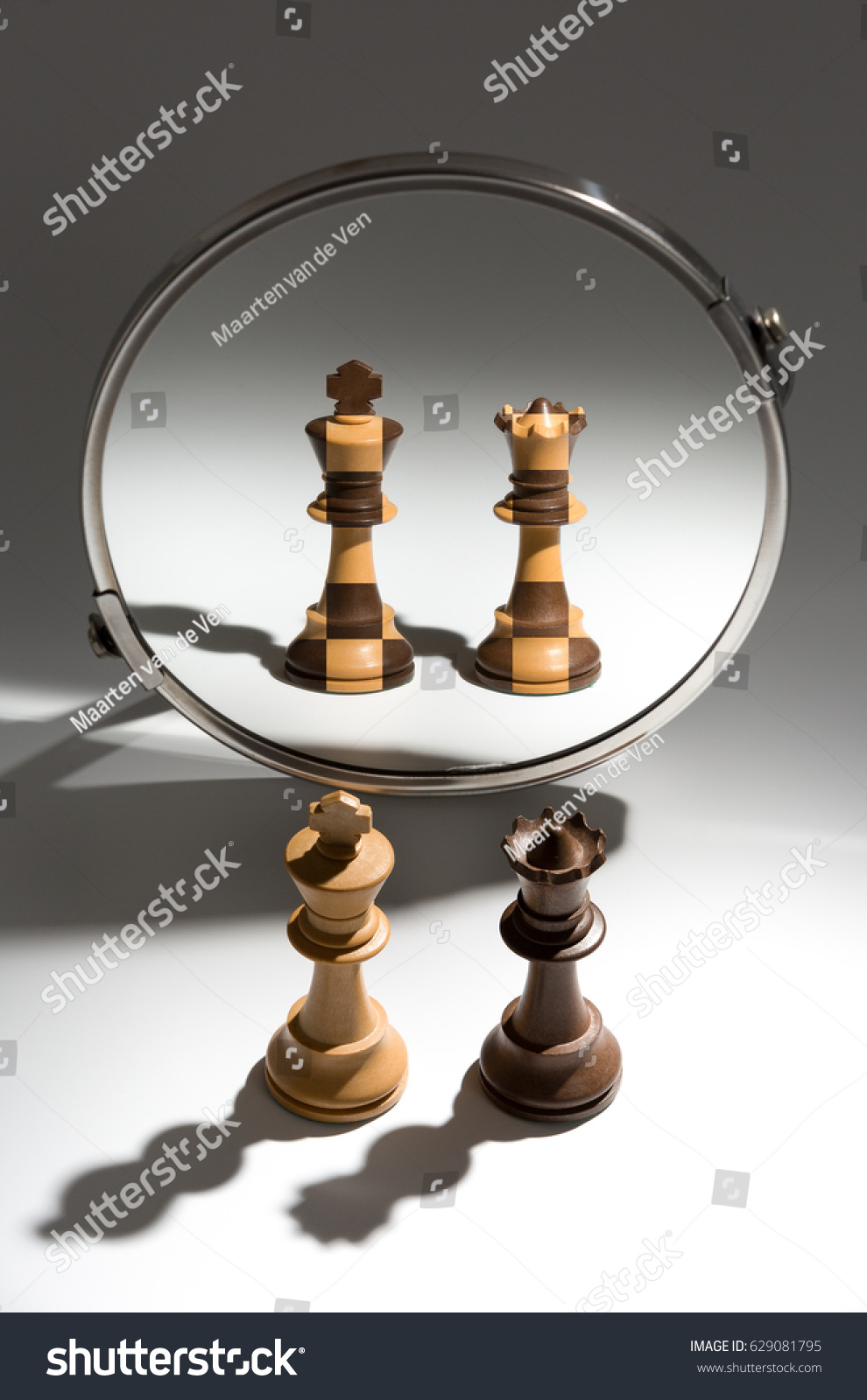 A couple of a white king and black queen chess pieces stand in front of a