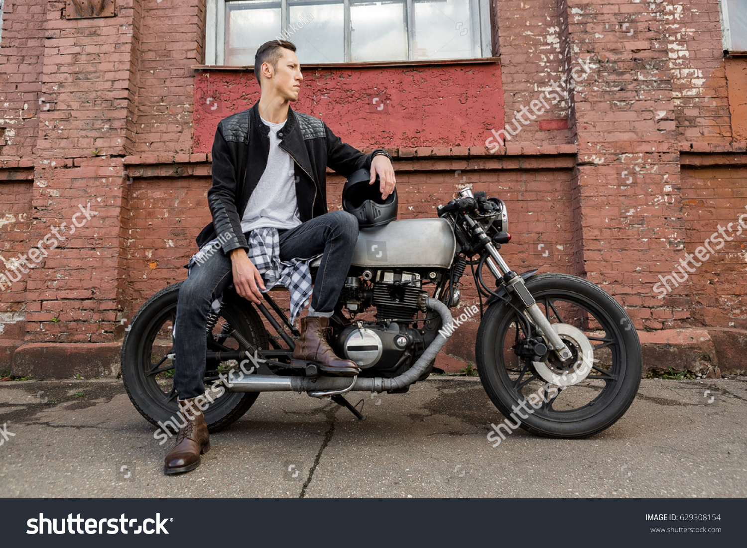 89b9df30 Handsome rider biker man in black leather jacket, jeans, boots and helmet  sit on