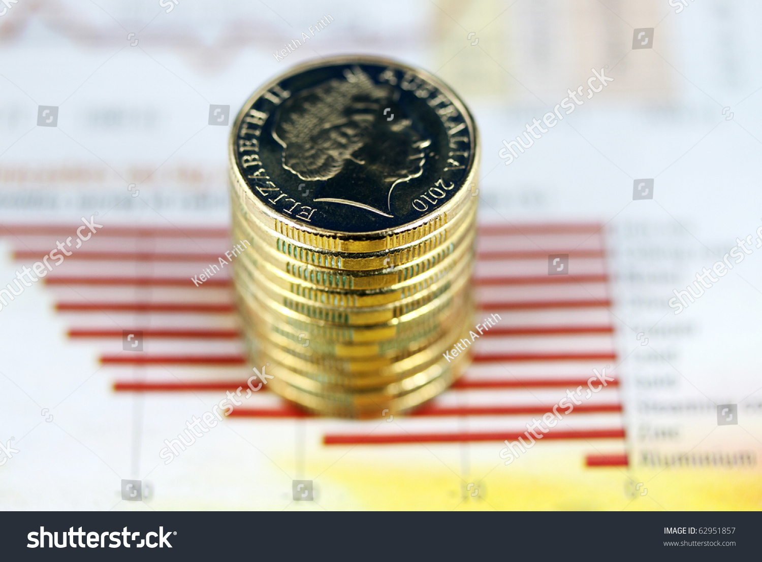 Some gold coins stacked on a newspaper… Stock Photo 62951857