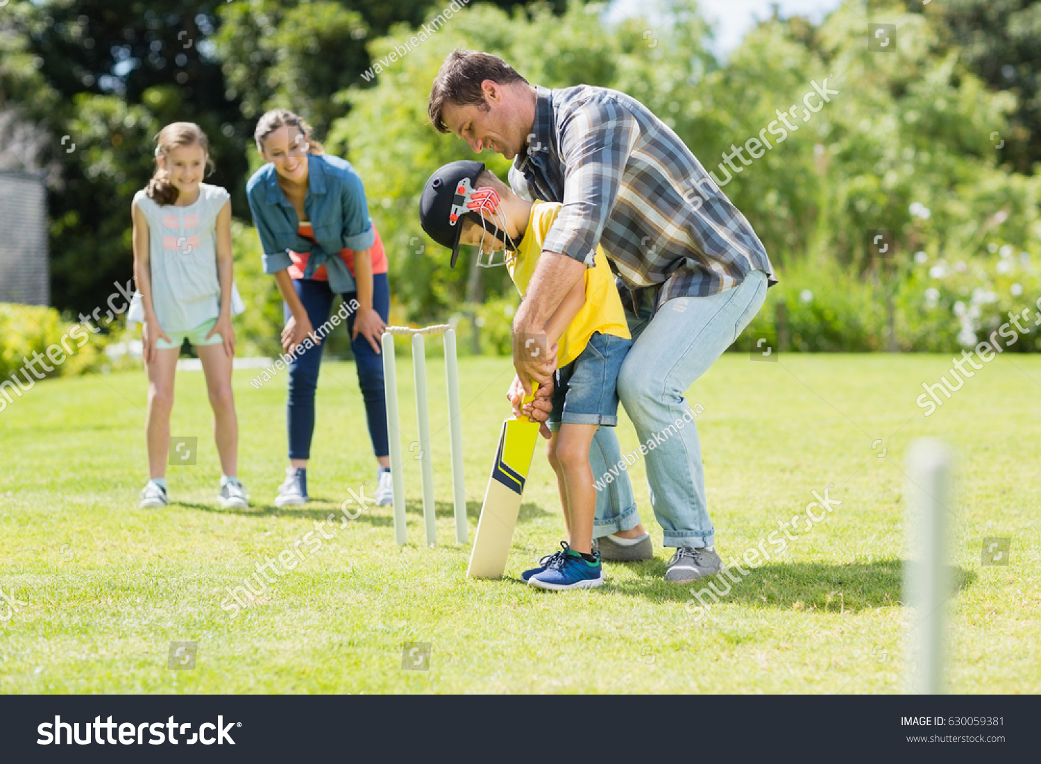 happy family playing cricket together backyard stock photo