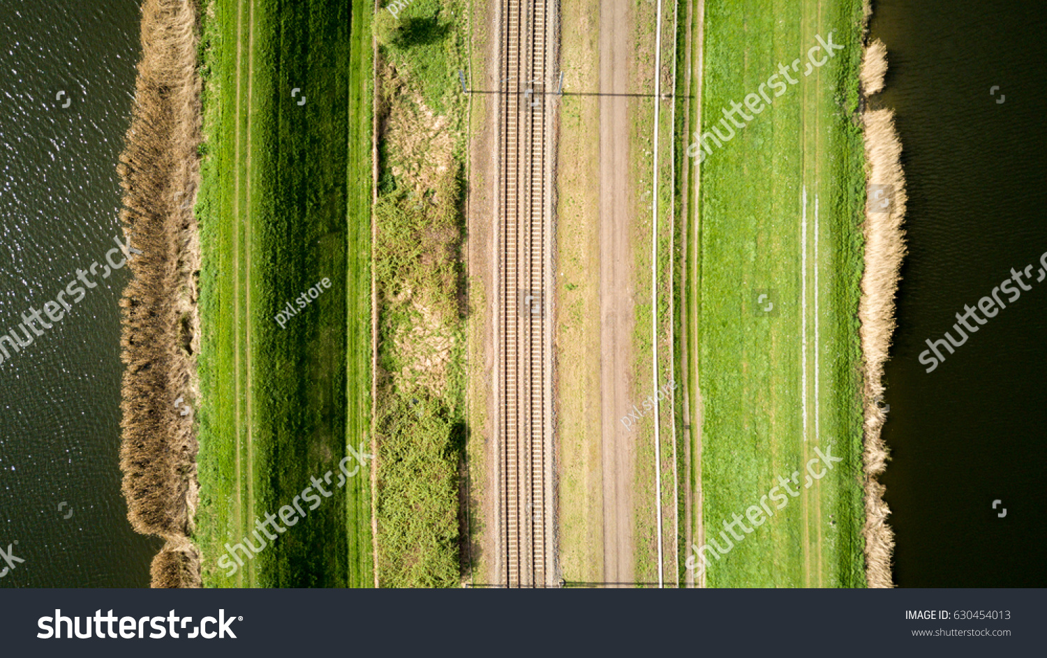 Vertical view of train tracks. Aerial drone photo of a train track bordered by water and pathways creating abstract mirrored lined textures.